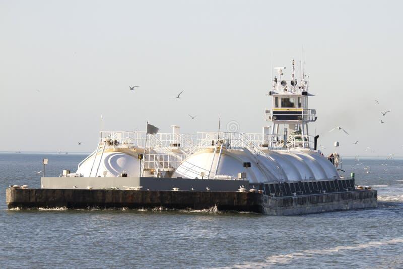 Les oiseaux marins suivant la péniche de transport de pétrole et de gaz photographie stock