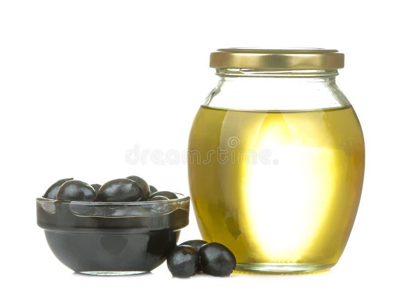 les olives noires avec l'huile et les feuilles d'olive se ferment sur un fond d'isolement blanc photo stock