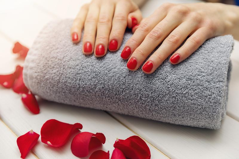 les ongles de femme avec le vernis à ongles rouge sur la serviette roulent image stock