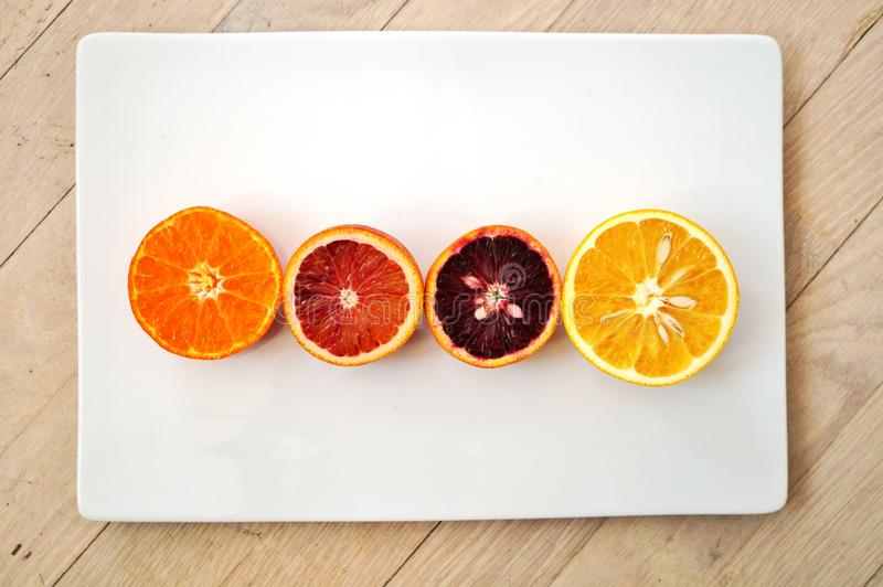 Les oranges sanguines rouges rouges, les oranges navel, et les clémentines ont coupé dans la moitié image stock