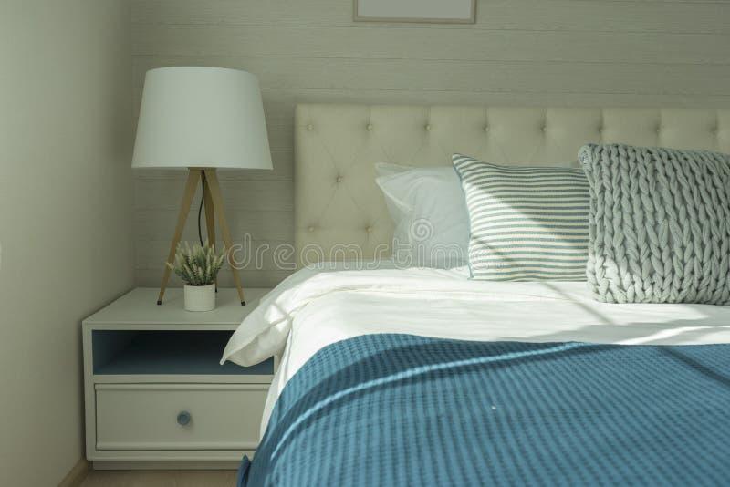 Les oreillers et la lampe avec le lit de toile blanc photo libre de droits