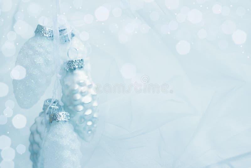 Les ornements de cônes de pins avec bokeh et paillettes; Carte de voeux de Noël en couleur argent bleu, avec espace de copie images libres de droits