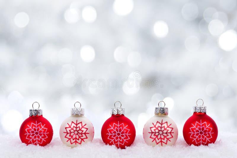 Les ornements de Noël rouge et blanc avec le scintillement argentent le fond photographie stock libre de droits