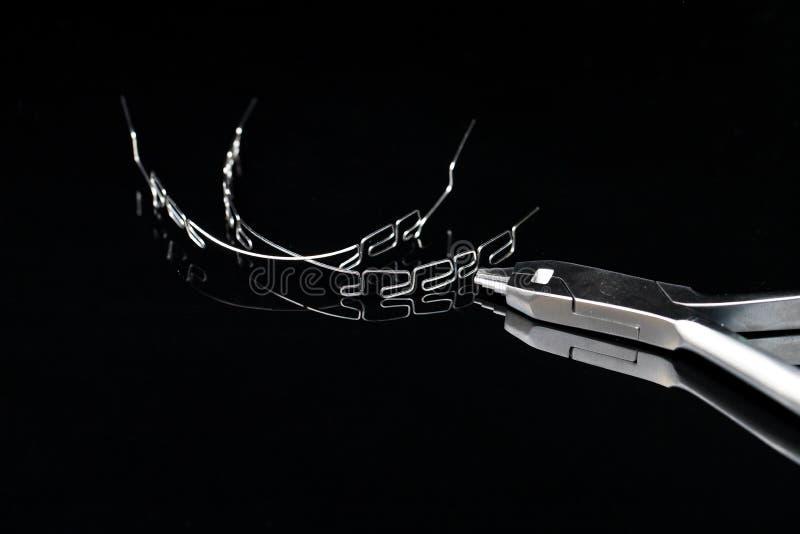 Les orthodonties usinent le système multiboucle d'accolades, sur le fond noir photos stock
