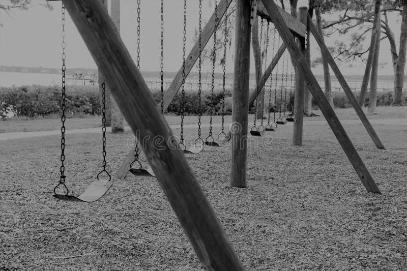 Les oscillations abandonnées vides noires et blanches en parc local reflètent notre enfance oublié image libre de droits