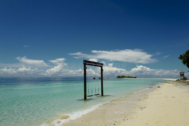 Les oscillations en bois sur la mer dans la perspective du ciel bleu photo libre de droits