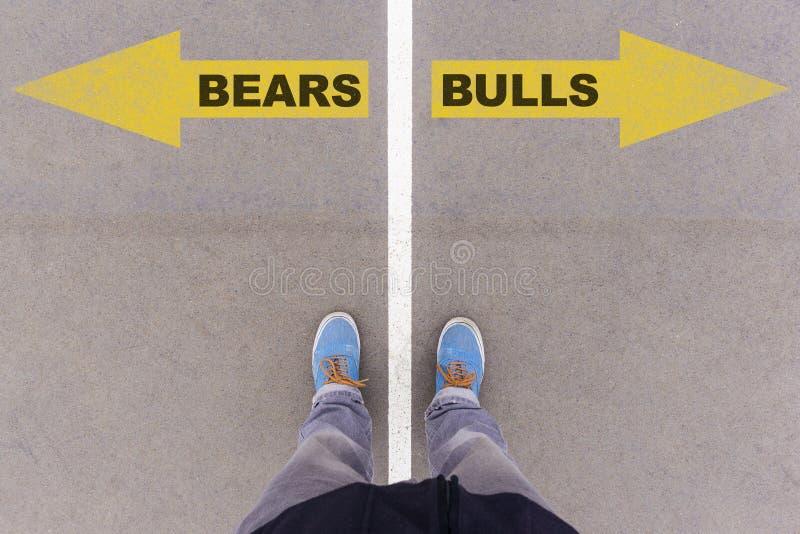 Les ours contre des taureaux textotent des flèches sur l'au sol, les pieds et les chaussures d'asphalte dessus photos stock