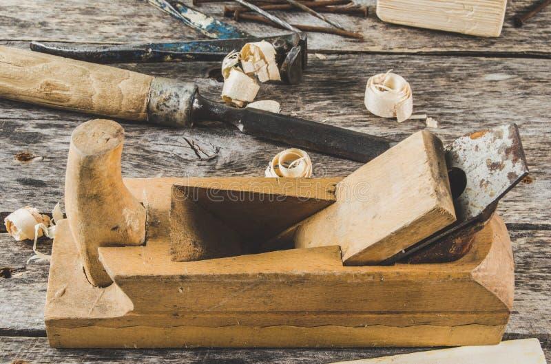 Les outils de charpentier sur le banc en bois, avion, burin, maillet, pinces, pinces, clous photo stock