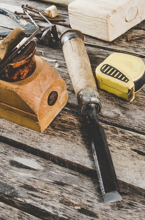Les outils de charpentier sur le banc en bois, l'avion, le burin, le maillet, le ruban métrique, les pinces, les clous et une sci photographie stock libre de droits