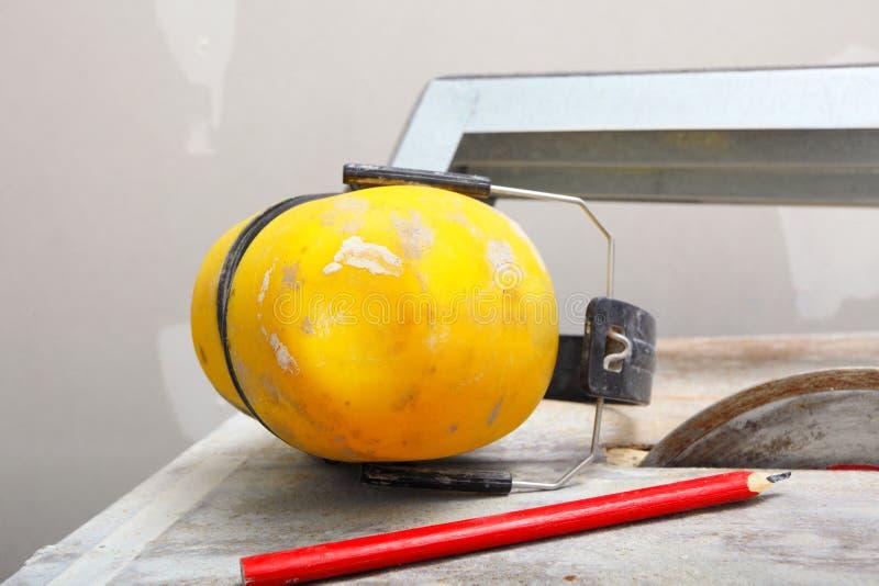 Les outils de travail ont vu le coupeur pour couper la tuile, écouteurs protecteurs images stock