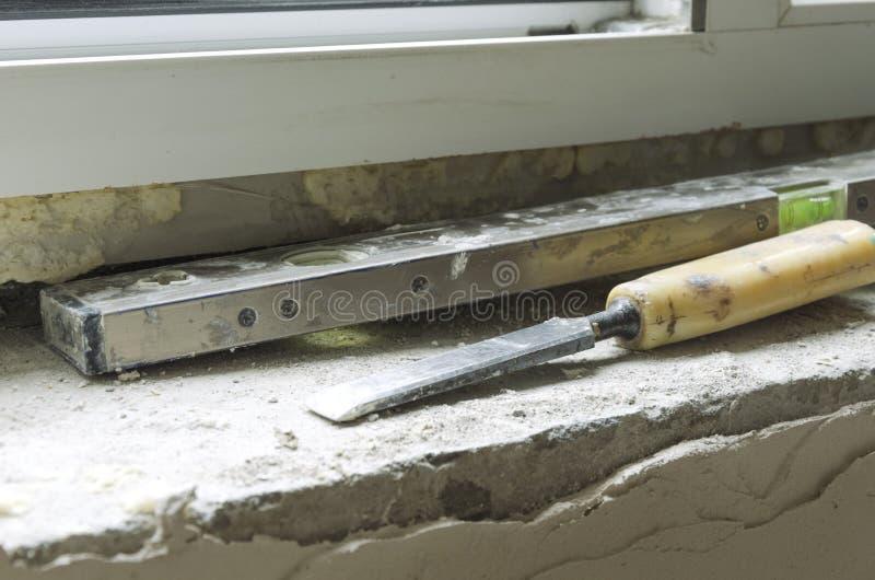 Les outils du constructeur Vieux niveau et burin d'esprit sur le filon-couche en pierre de fenêtre photographie stock libre de droits