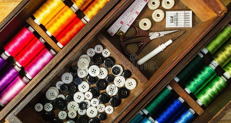 Les outils et les accessoires de couture avec les fils colorés maintiennent dans la vieille boîte en bois photographie stock libre de droits