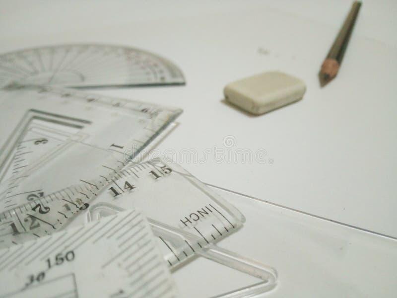 Les outils, la gomme et le crayon de rédaction sont sur le fond blanc photographie stock