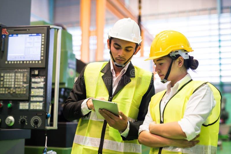 Les ouvriers de l'usine vérifient le stock dans la tablette image libre de droits