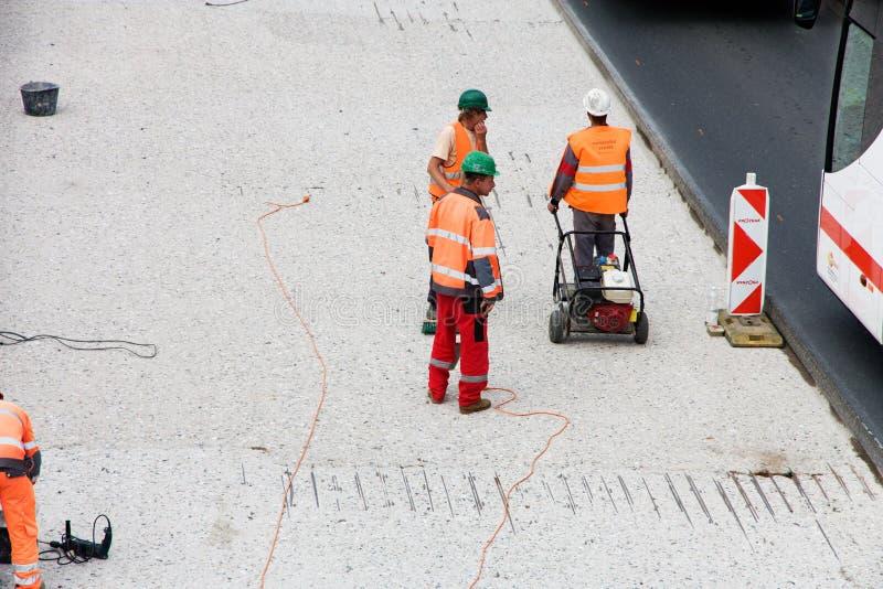 Les ouvriers réparent la route photo stock