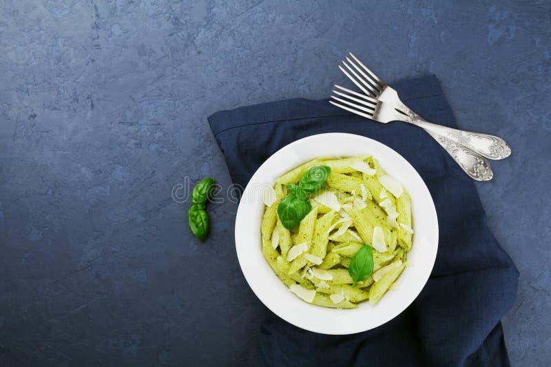 Les pâtes avec de la sauce à pesto ont décoré les feuilles de basilic et le parmesan dans le plat blanc sur la table ci-dessus de image libre de droits