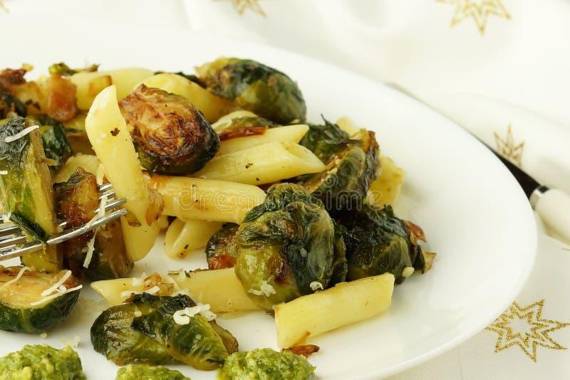 Les pâtes avec les légumes verts ont rôti les choux de Bruxelles et la sauce à pesto photographie stock libre de droits