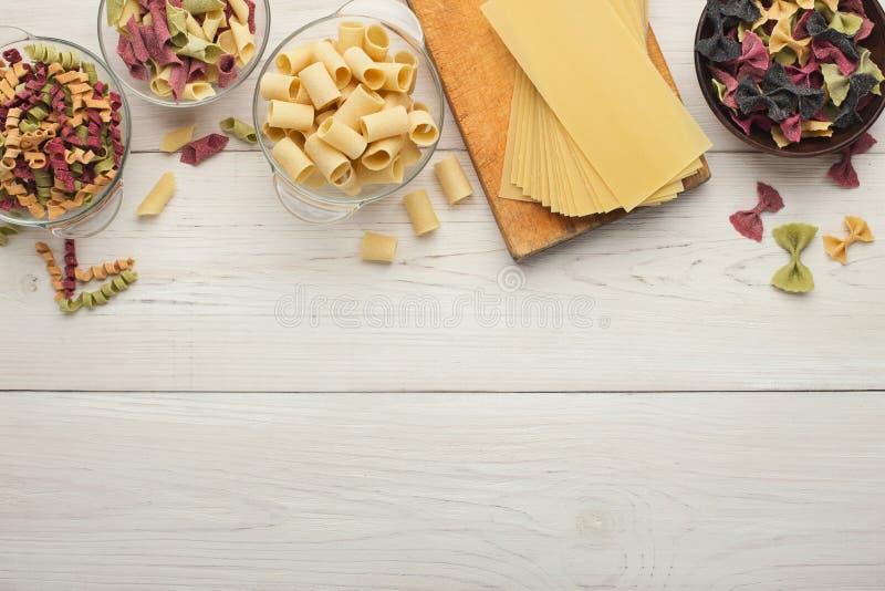 Les pâtes colorées assorties roulent sur le bois blanc, vue supérieure photos stock