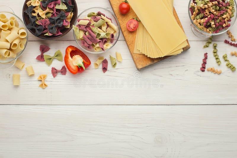 Les pâtes colorées assorties roulent sur le bois blanc, vue supérieure image stock