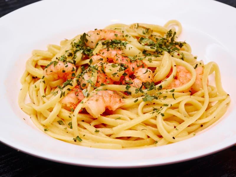 Les pâtes de linguine de crevette rose avec le basilic ont servi sur un plat blanc photo stock