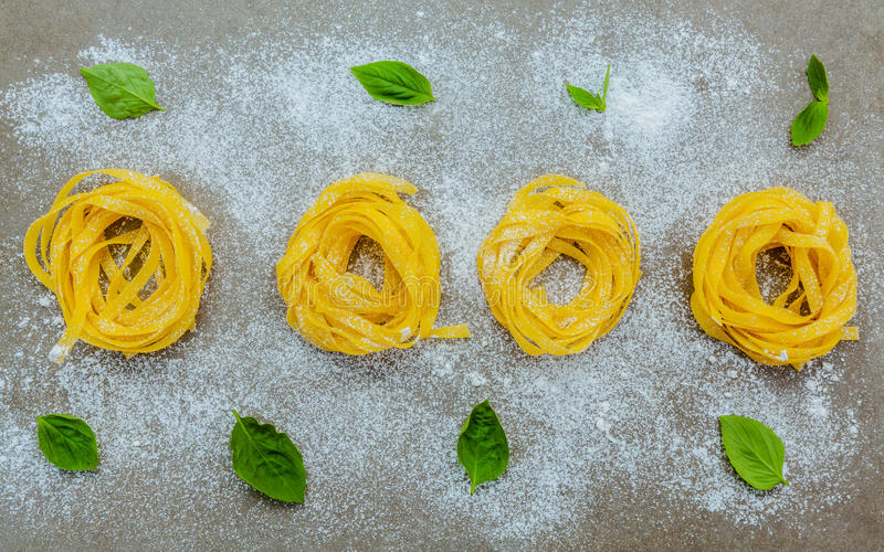 Les pâtes italiennes de concept de nourriture avec le basilic doux avec de la farine ont installé dessus photographie stock