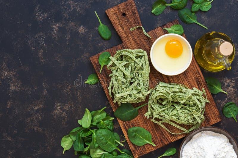 Les pâtes vertes crues avec des épinards, épinards partent, flour, oeuf sont cassées dans une cuvette sur un fond bleu-foncé Vue  photographie stock