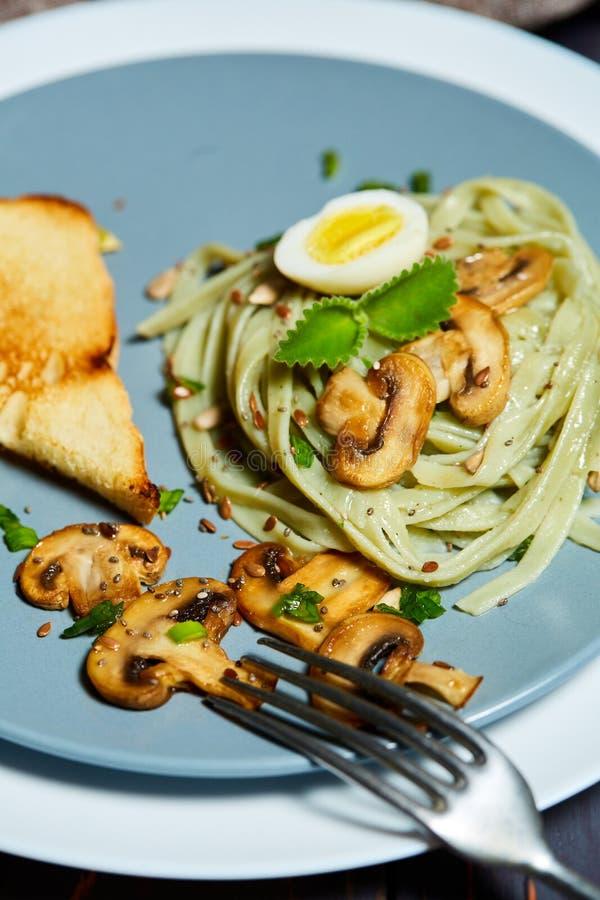 Les pâtes vertes d'épinards avec des légumes répandent des oeufs de tost et de caille de blé photographie stock libre de droits