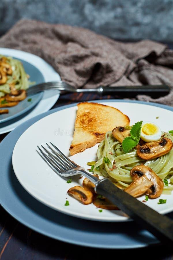 Les pâtes vertes d'épinards avec des légumes répandent des oeufs de tost et de caille de blé photo stock
