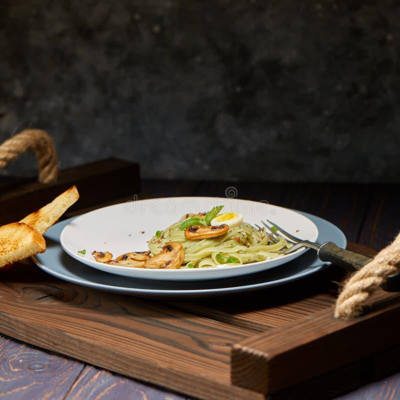 Les pâtes vertes d'épinards avec des légumes répandent des oeufs de tost et de caille de blé image libre de droits