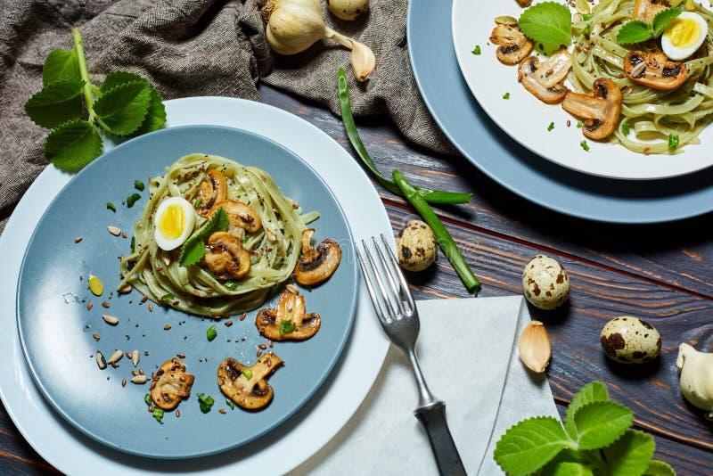 Les pâtes vertes d'épinards avec des légumes répandent des oeufs de tost et de caille de blé images libres de droits