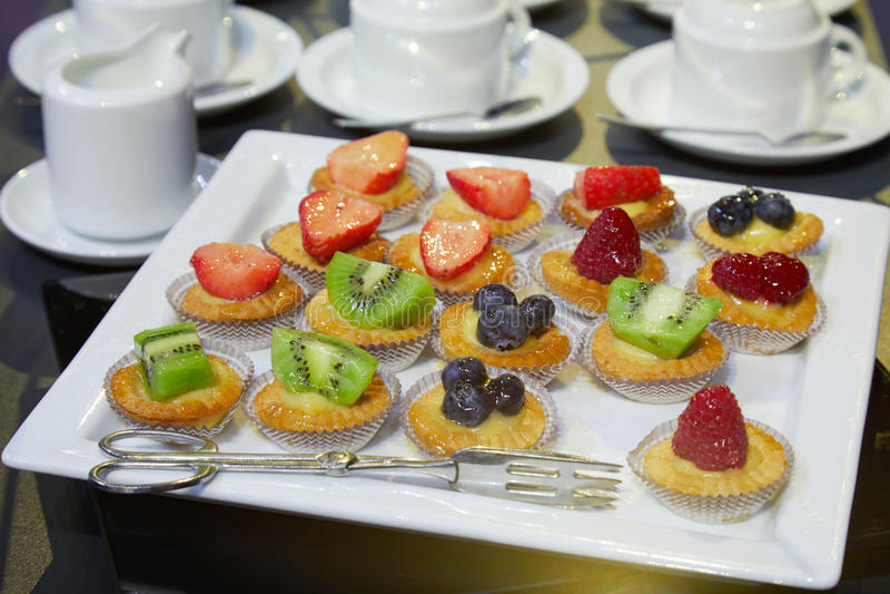 Les pâtisseries avec des tasses de fruit et de café pour l'hôtel déjeunent photographie stock