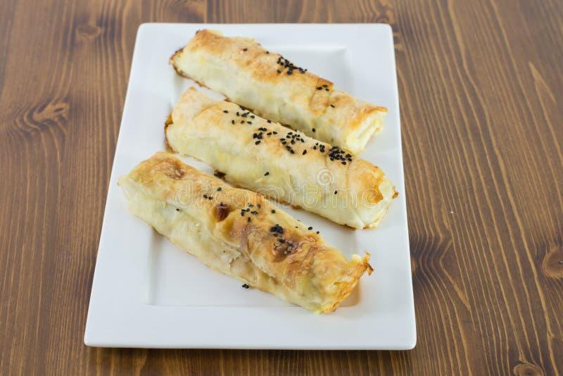 Les pâtisseries cuites au four fraîches avec du fromage et le rassemblement ont servi du plat blanc sur la table en bois photo libre de droits