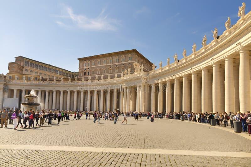 Les pèlerins et les touristes font la queue sous le colomnade attendant pour entrer en basilique de St Peter photographie stock libre de droits
