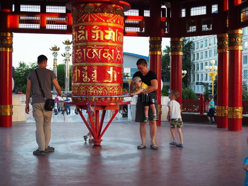 Les pères avec des enfants de différentes nationalités marchent autour des roues bouddhistes de tambour de prière rouge La Russie images stock