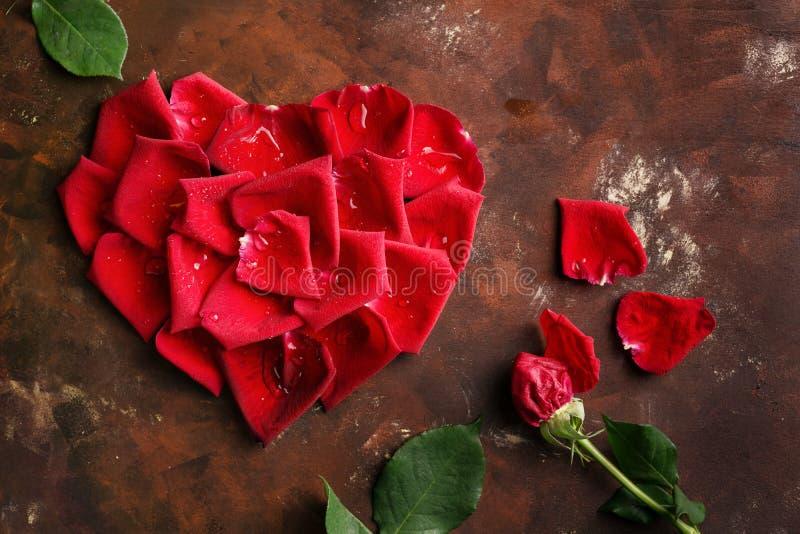 Les pétales de rose rouges au coeur forment sur le brun foncé et le fond d'or Aimez, romance, anniversaire, concept de jour du `  photographie stock