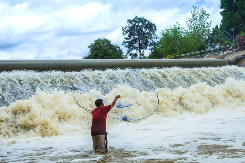 Les pêcheurs, jettent un filet, pêcheurs jettent un filet sur le barrage en caoutchouc image stock