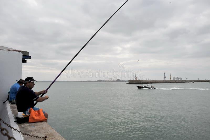 Les pêcheurs pêchent dans le port du port maritime de Cadix photographie stock libre de droits