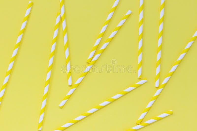 Les pailles de papier barrées ont dispersé sur un fond jaune Configuration plate estivale lumineuse photographie stock libre de droits