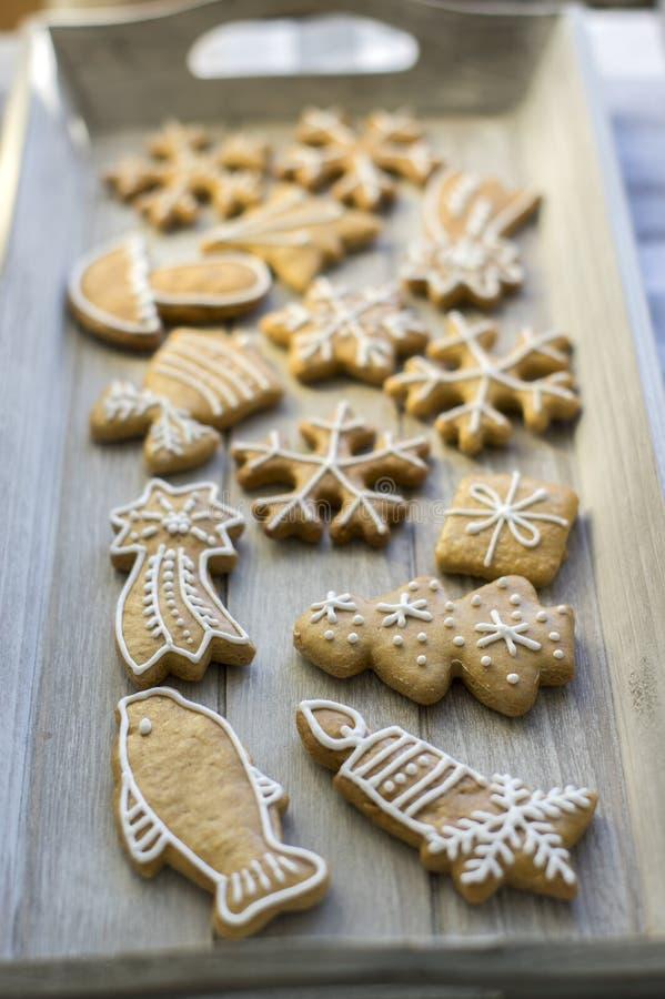 Les pains d'épice traditionnels peints de Noël ont arrangé sur le plateau en bois en journée, les flocons de neige et d'autres sy photos libres de droits