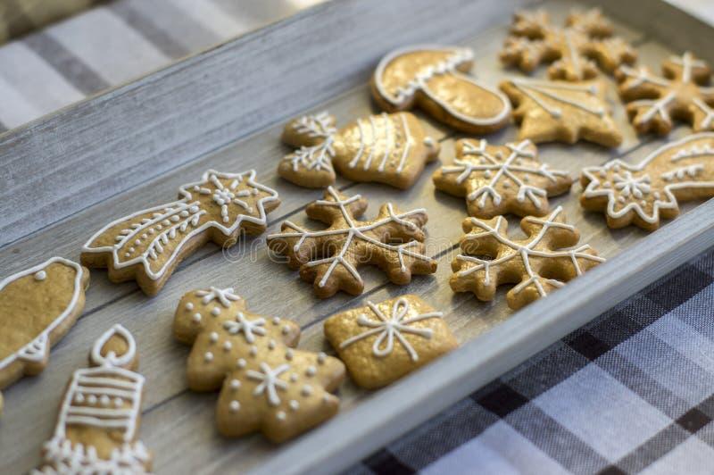 Les pains d'épice traditionnels peints de Noël ont arrangé sur le plateau en bois en journée, les flocons de neige et d'autres sy photographie stock libre de droits