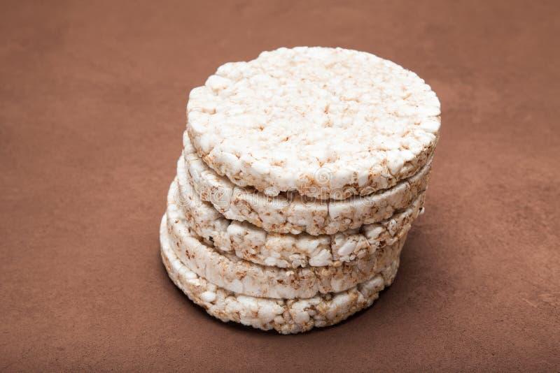 Les pains diététiques de riz ont présenté par une pyramide Fond de Brown photographie stock