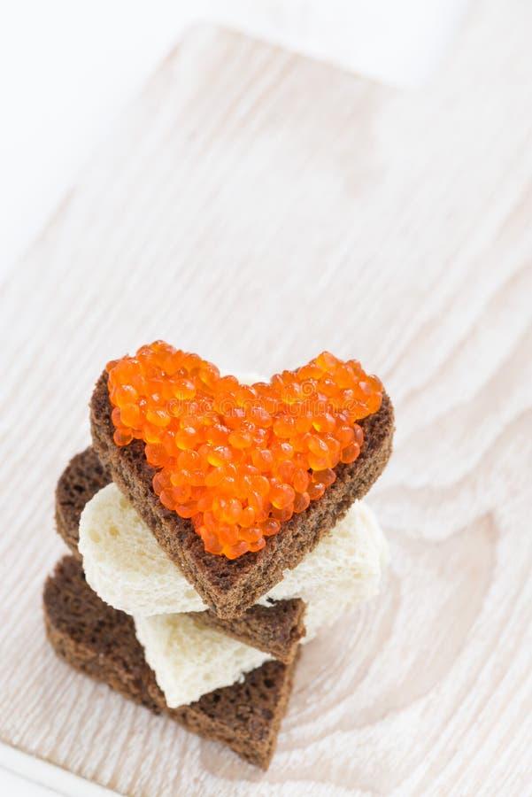 Les pains grillés avec le caviar rouge au coeur forment sur le panneau en bois, vue supérieure photographie stock libre de droits