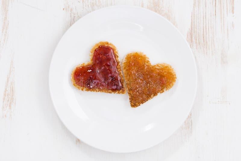 Les pains grillés dans la forme de coeur avec le fruit bloquent du plat, vue supérieure image libre de droits