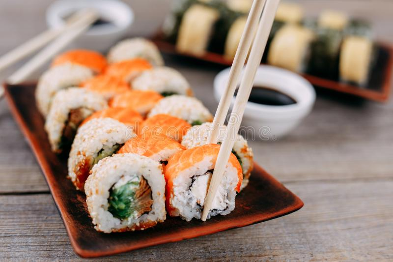 Les paires de baguettes prenant le petit pain de sushi, se ferment  photo libre de droits