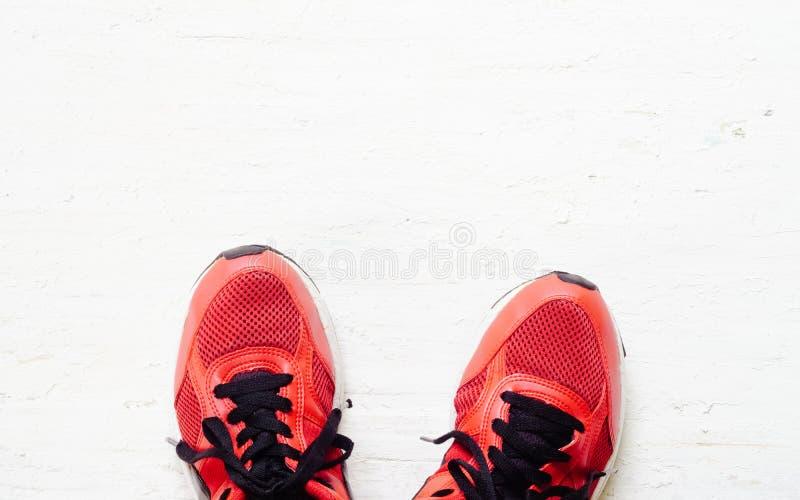 Les paires de chaussures rouges de sport se sont étendues sur le backgr en bois blanc grunge de plancher photo libre de droits