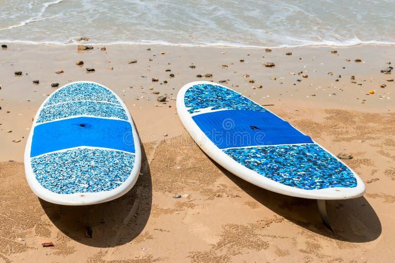 Les paires de planches de surf se trouvent sur une plage sablonneuse images libres de droits