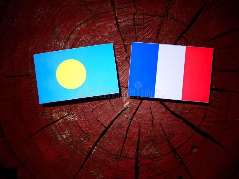 Les Palaos diminuent avec le drapeau français sur un tronçon d'arbre d'isolement photos stock