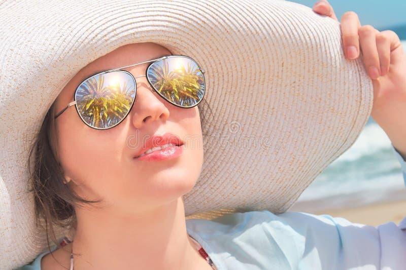 Les palmiers se reflètent dans les lunettes de soleil, portrait d'une femme dans le chapeau photo stock