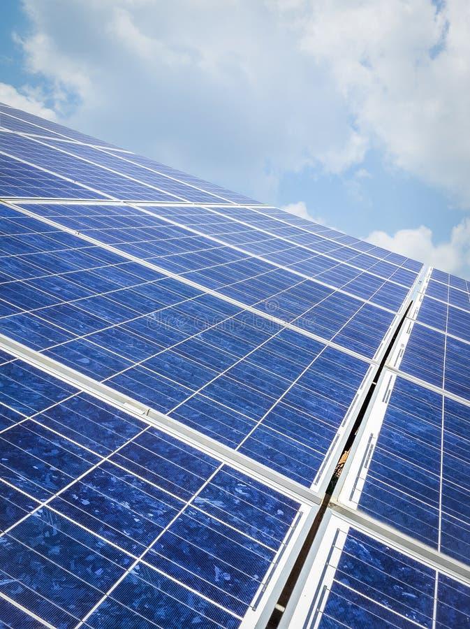 Les panneaux solaires cultivent sur une belle verticale de fond de ciel bleu images stock