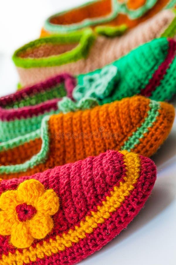 Les pantoufles faites maison tricotées lumineuses et colorées photographie stock libre de droits